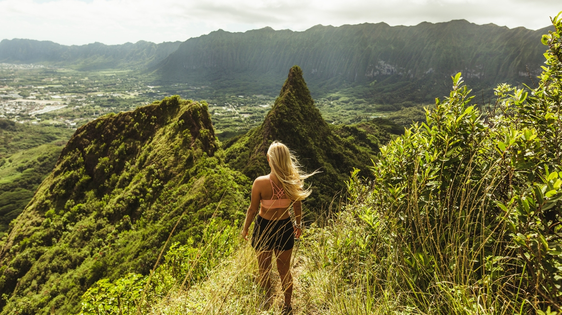 Rear view of woman on grass covered mountain, Oahu, Hawaii, USA
