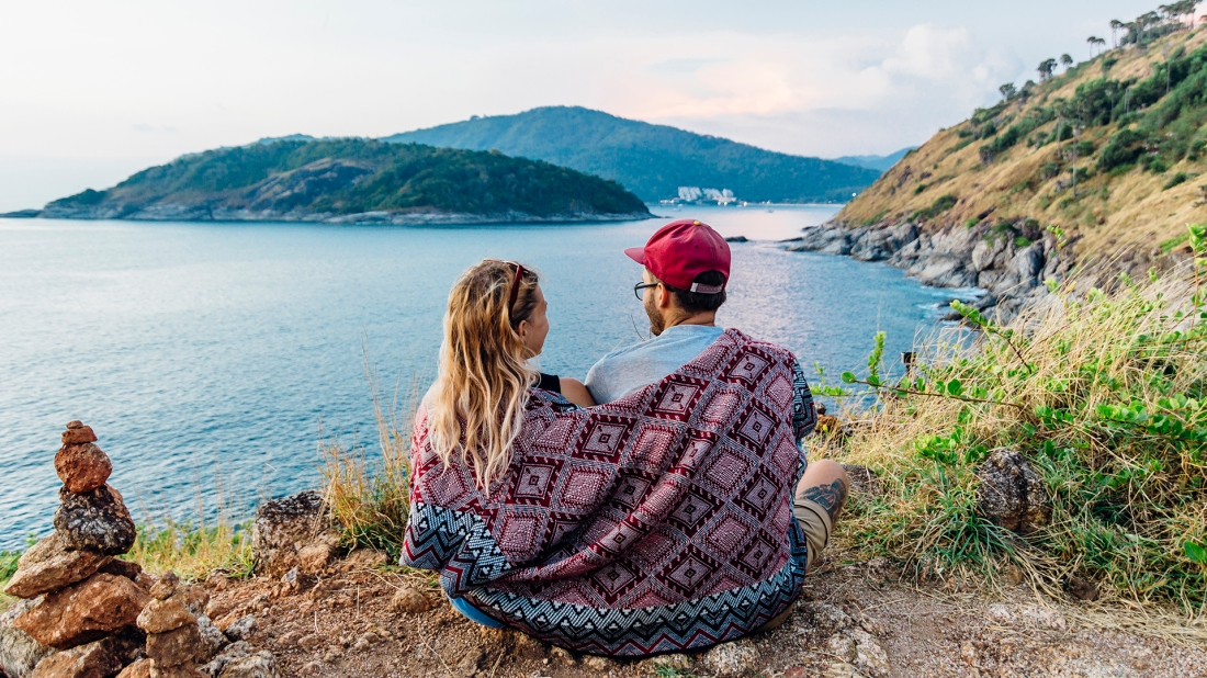Young couple relax under blanket, on hillside above sea