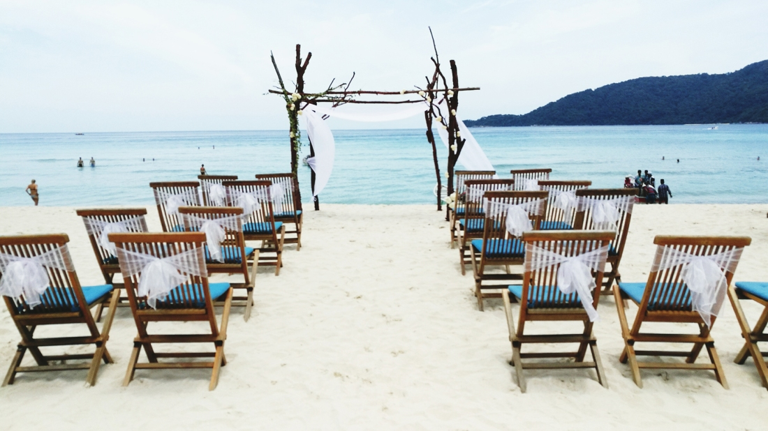 Empty Chairs Arranged At Sandy Beach For Wedding Ceremony